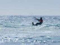 Young man in a dark waterproof suit is engaged in kiteboarding in windy weather on the Mediterranean Sea near Nahariyya, Israel. Nahariyya, Israel - Februar 10 Royalty Free Stock Photography