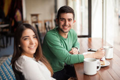 Young man on a date drinking some coffee. Portrait of a handsome young men having a good time with his girlfriend in a coffee shop Stock Images