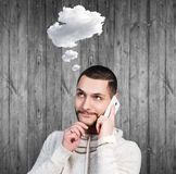 Young man daydream and speak on the phone. With cloud owerhead on the wooden background Stock Photography