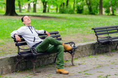 Young man daydreaming on the bench in the park Stock Photography