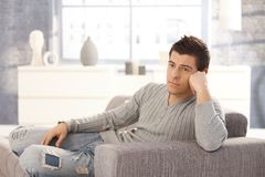 Young man daydreaming on sofa Royalty Free Stock Photos