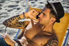 Young man on deckchair at beach talking on phone Stock Photography