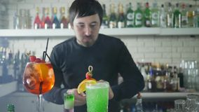 Young man decorates delicious cocktail with tropical fruits and strawberries in light smoke on background bottles. Young man decorates delicious cocktail with stock video footage