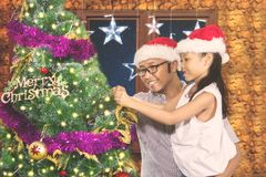 Young man decorates a fir tree with daughter Stock Photo