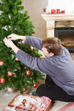 Young man decorating christmas tree at home with chimney. Royalty Free Stock Photos