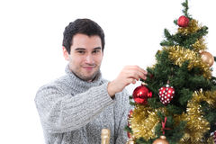 Young man decorating Christmas tree stock images