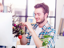 Young man decorating christmas tree in office Stock Image