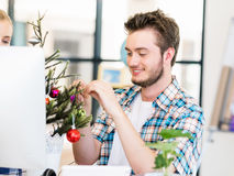Young man decorating christmas tree in office Royalty Free Stock Photography