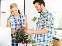 Young man decorating christmas tree in office Royalty Free Stock Image