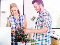 Young man decorating christmas tree in office Stock Photography