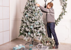 Young man decorating green christmas tree with lights and balls. Stock Image