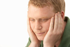 Young man deep in thought. With hands on cheeks royalty free stock image