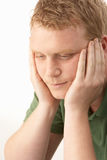 Young man deep in thought. With hands on cheeks stock photography