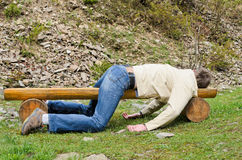 Young man deeply sleeping on. Young man deeply sleeping or drunk, laying outdoors on a wooden park bench. Profile view Stock Image