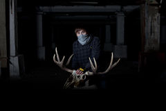 Young man with a deer skull in front of him in dark cellar Royalty Free Stock Photos