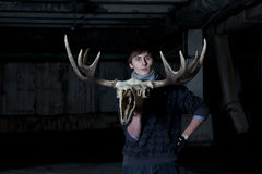 Young man with a deer skull with horns Stock Photography