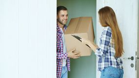 Young man deliver cardboard box to customer at home. Woman sign in clipboard for receiving parcel. Young men deliver cardboard box to customer at home. Woman Royalty Free Stock Photo