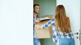 Young man deliver cardboard box to customer at home. Woman sign in clipboard for receiving parcel Stock Photos