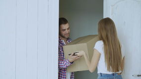 Young man deliver cardboard box to customer at home. Woman write digital signature on tablet computer for receiving stock video footage