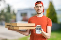 Young man is delivering pizza in boxes and holds payment terminal. Stock Photography