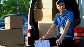 Young man from delivery service resting, sitting in van, loading of parcels royalty free stock photos