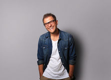 Young man in a denim shirt is smiling. Young man in a denim shirt and glasses is smiling Royalty Free Stock Photos