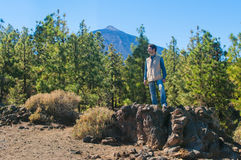 Young man in denim standing on rocks and looking away Royalty Free Stock Photography