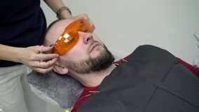 Young man in dental chair. Young man sitting in dental chair wearing orange glasses stock footage