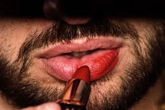 A young man depicts his lips with red lipstick. royalty free stock photography