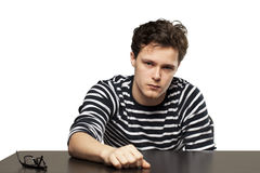Young man depressed at table Stock Images