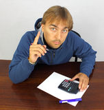 Young man at the desk with calculator Royalty Free Stock Images