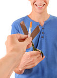 Young Man destroy a Cigarette. Young Man cutting a Cigarette with Scissors Isolated on the White Background stock photo
