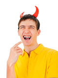 Young Man with Devil Horns. Cheerful Young Man with Devil Horns laughing Isolated on the White Background Royalty Free Stock Photos