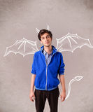 Young man with devil horns and wings drawing. Young nasty man with devil horns and wings drawing Royalty Free Stock Photos
