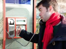 Young man dialing phone number at public phone box Royalty Free Stock Photography