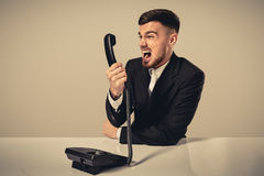 Young man dials the phone number while sitting in the office Royalty Free Stock Photos