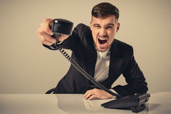 Young man dials the phone number while sitting in the office Stock Photos