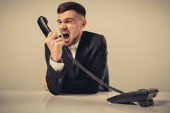 Young man dials the phone number while sitting in the office Stock Images