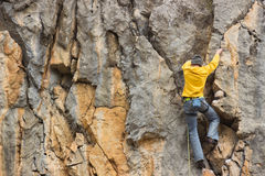 Young man on a difficult mountain route. Stock Photo