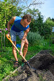 A young man digging a flower bed on the plot on a Sunny day Royalty Free Stock Photography