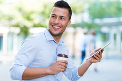 Young man with digital tablet and coffee outdoors Royalty Free Stock Photos