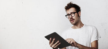 Young man with digital tablet in his hands. Portrait of a young man with digital tablet Royalty Free Stock Photo