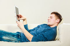 Young man with digital tablet laying on couch royalty free stock photography