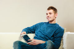 Young man with digital tablet sitting on couch Royalty Free Stock Image