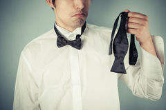 Young man ding a bow tie Royalty Free Stock Photography