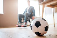 Young man with disability sitting on wheelchair and look down at ball for game. Ex sportsman. Upset and unhappy. Trauma. Can`t play football anymore royalty free stock images