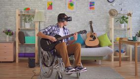 Young man disabled musician in a wheelchair and virtual reality glasses playing guitar stock video