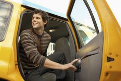 Young Man Disembarking Taxi Royalty Free Stock Photography