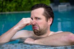 Young man with disgust on his face pinches nose, something stinks, very bad smell in swimming pool because of chloride. Negative emotion facial expression stock photos