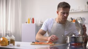 Young man disgusted with stinky meal on stove, spoiled ingredients, untasty food